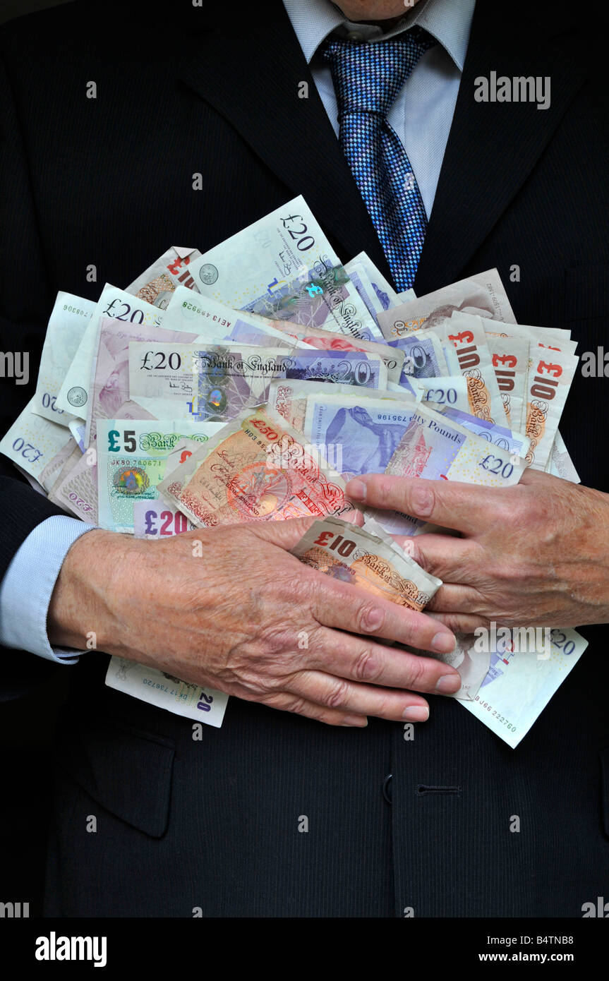 Model released man wearing office business suit hands clutching piles UK pound notes money concept for bankers, - Stock Image