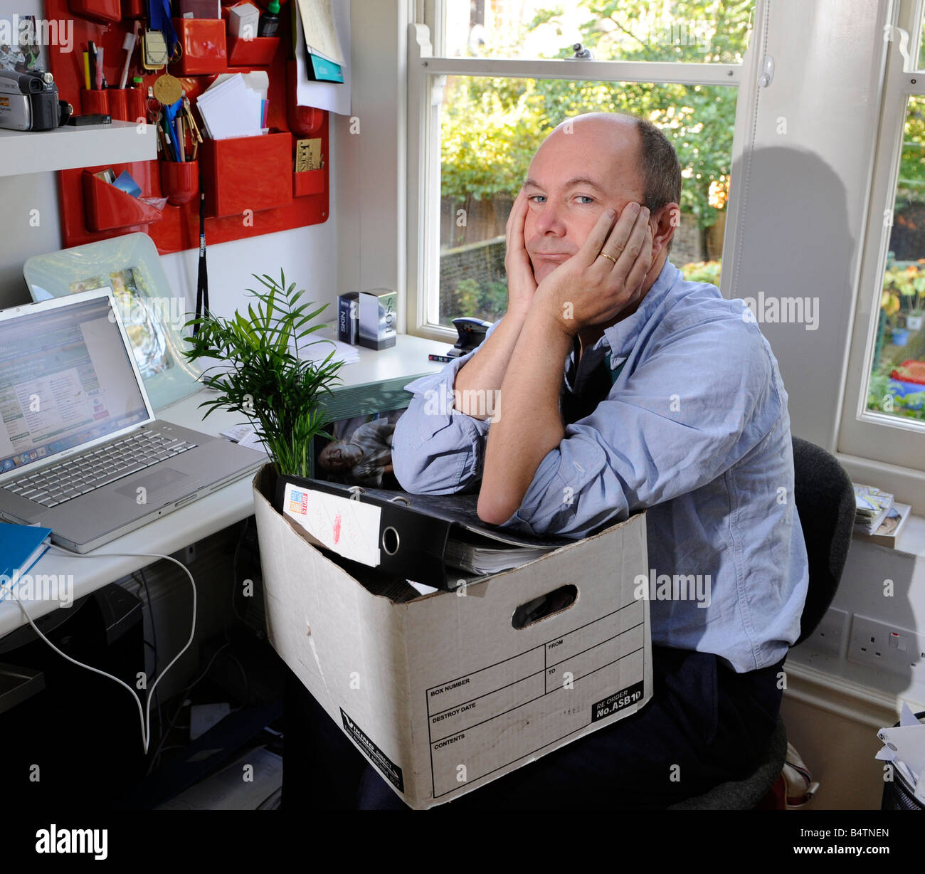 Sad and worried man packs up his desk and belongings after losing his job, being made redundant, being fired Stock Photo