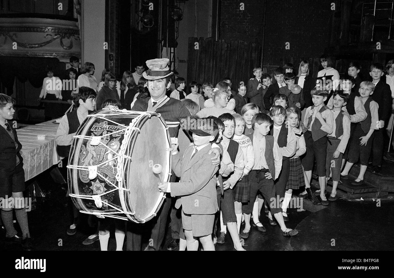 Lionel Bart who wrote Oliver plays the big drum from the Irish Guards as he marches round the Stage with the orphans - Stock Image
