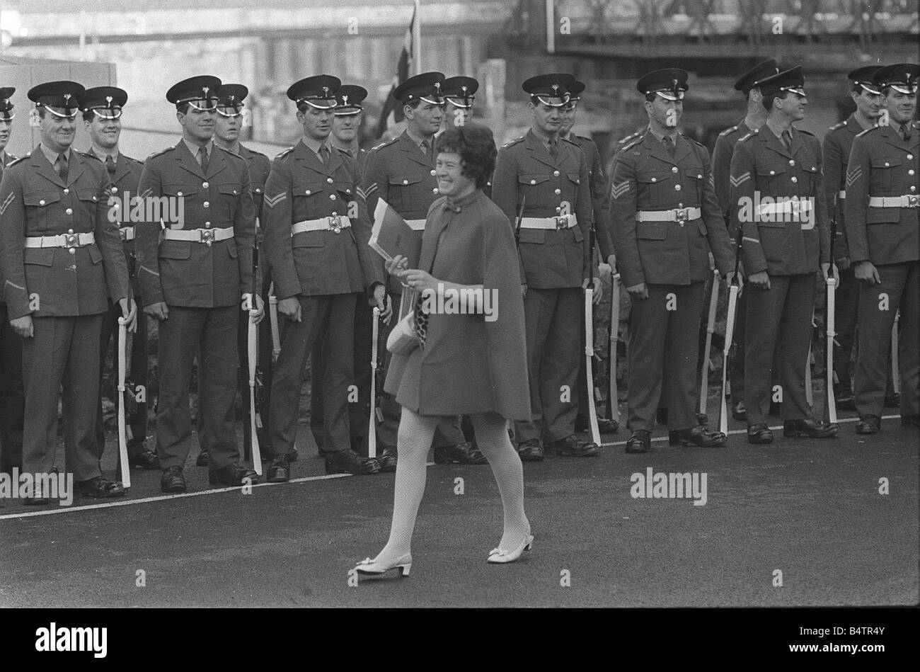 Investiture rehearsals Soldiers smile as a lady in a mine dress and coat walks past their parade line up 1 7 69 - Stock Image