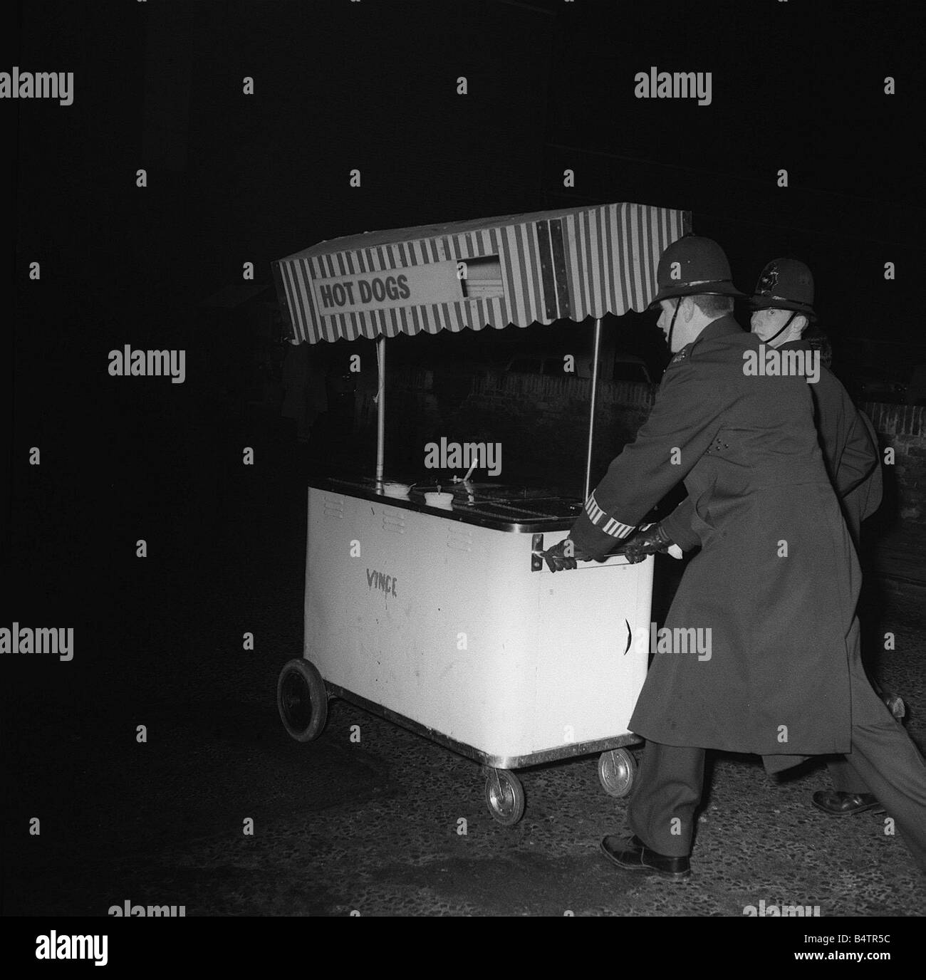 Policemen with hot dog stand Ello ello ello What have we here then Not as it may appear a couple of rogue police Stock Photo