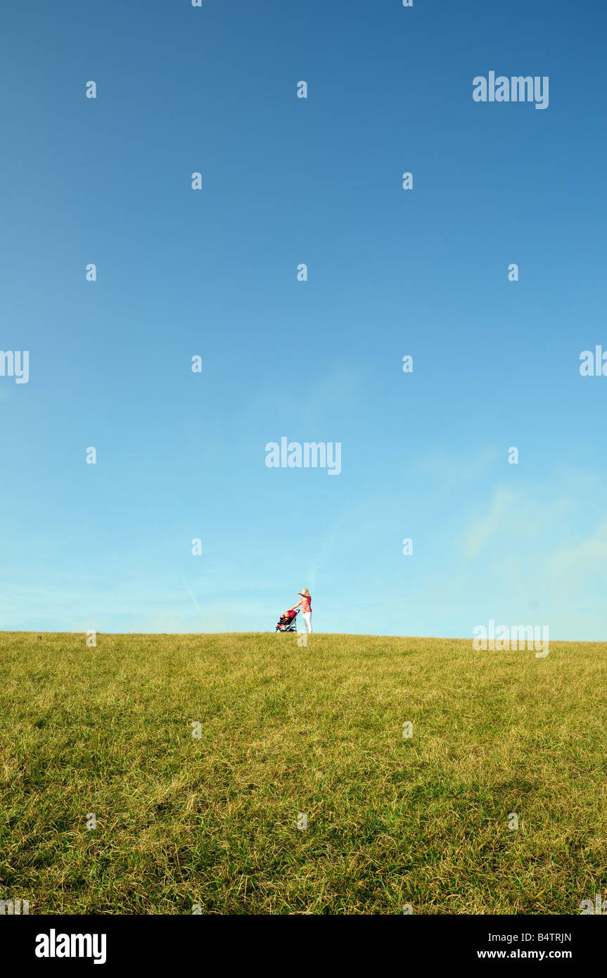 Single mother pushing child in push chair over green field - Stock Image
