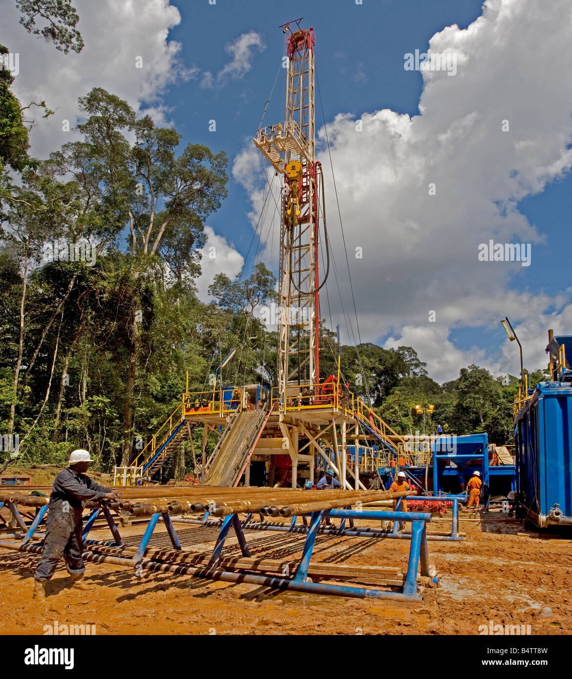 Remote onshore oil well and drillrig site in rainforest with crewmen