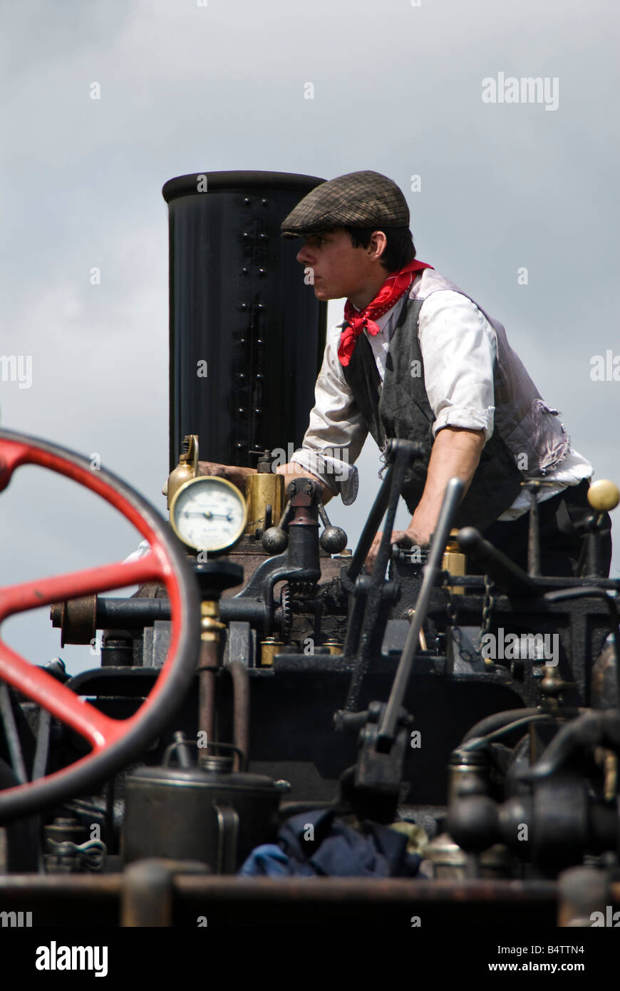 A young enthusiast in traditional dress maintans a steam traction engine at a vintage vehicle show. UK - Stock Image