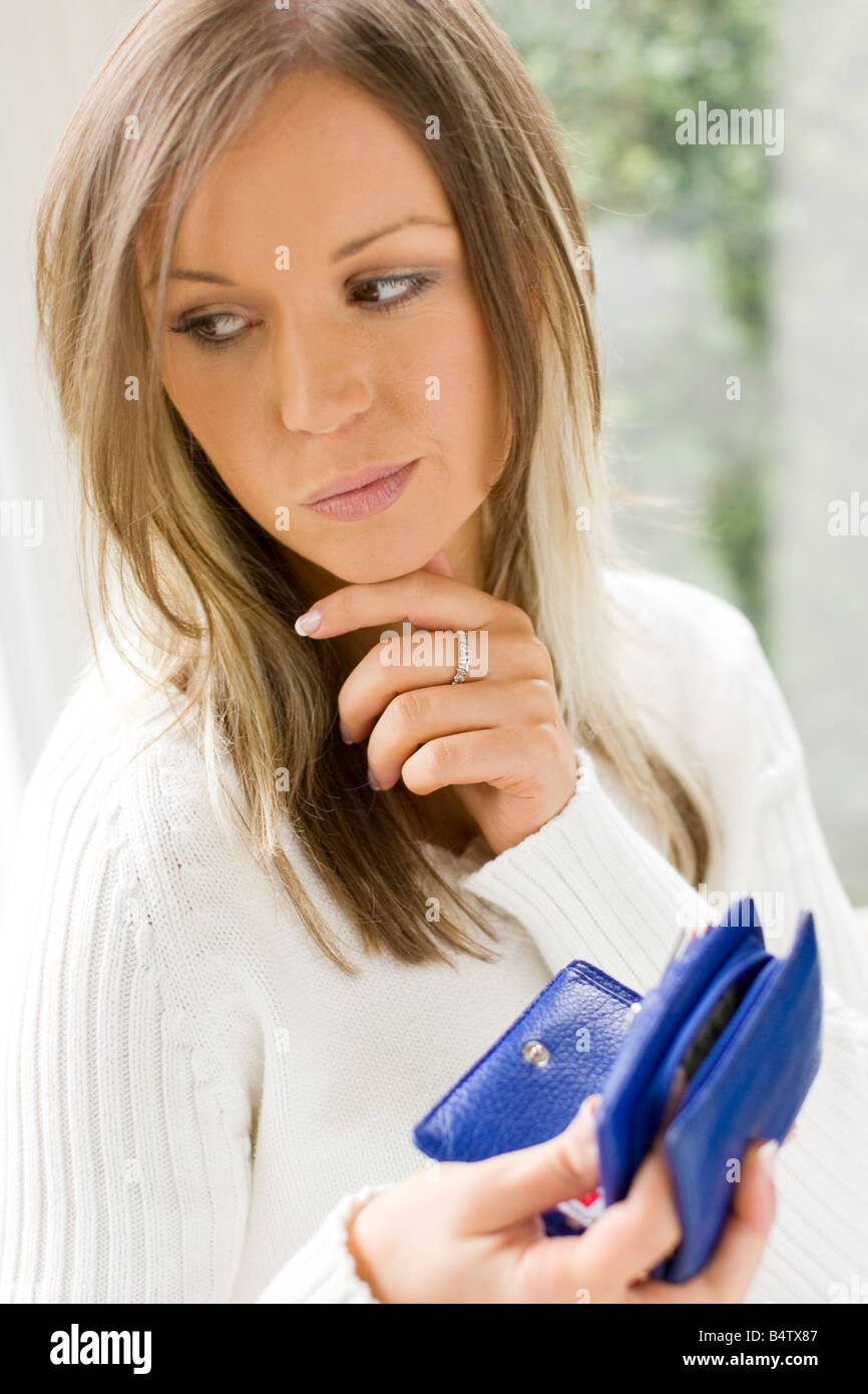 young woman putting coins in purse - Stock Image