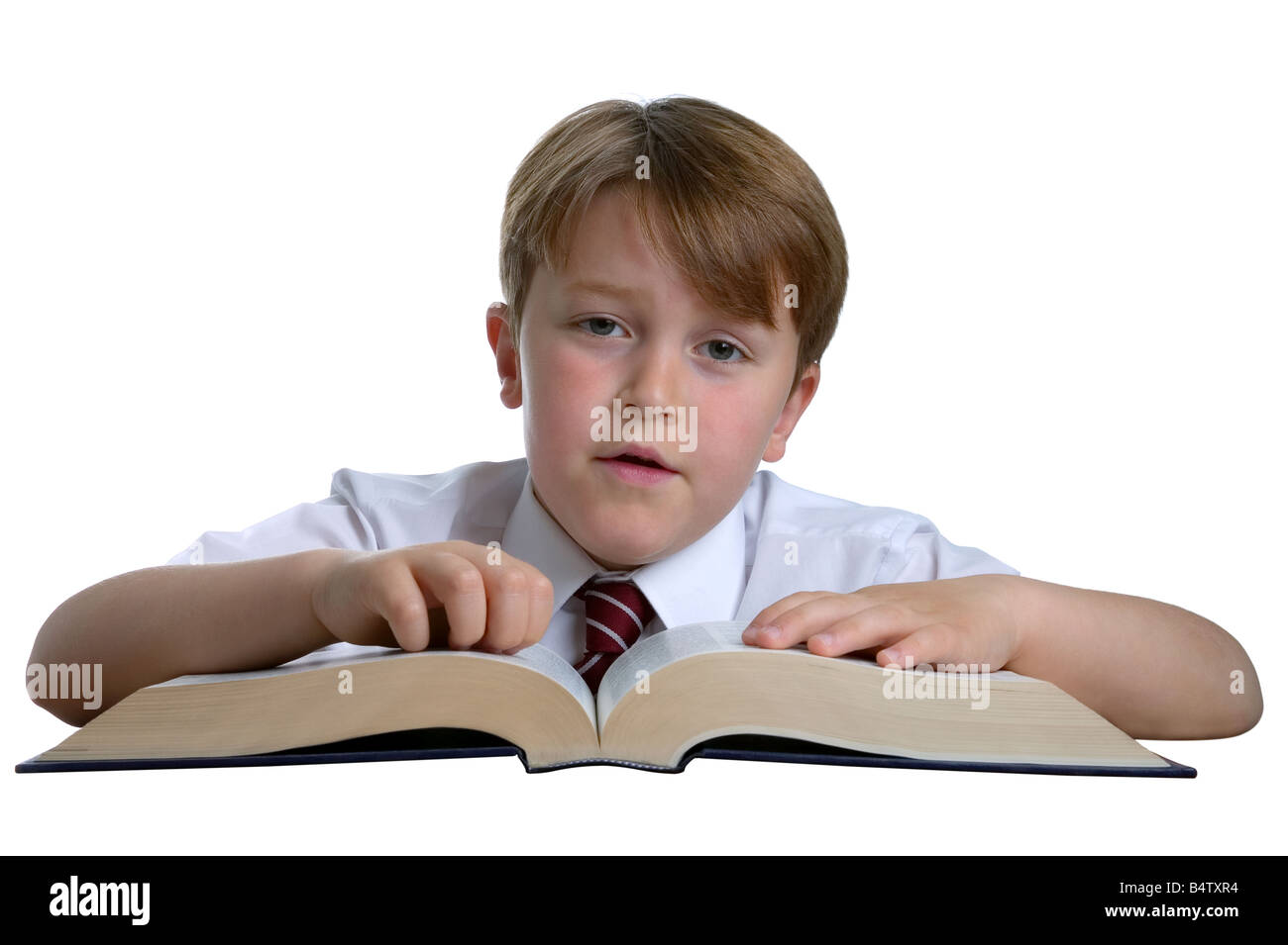 Cut out of a Schoolboy with a reference book looking at the camera - Stock Image