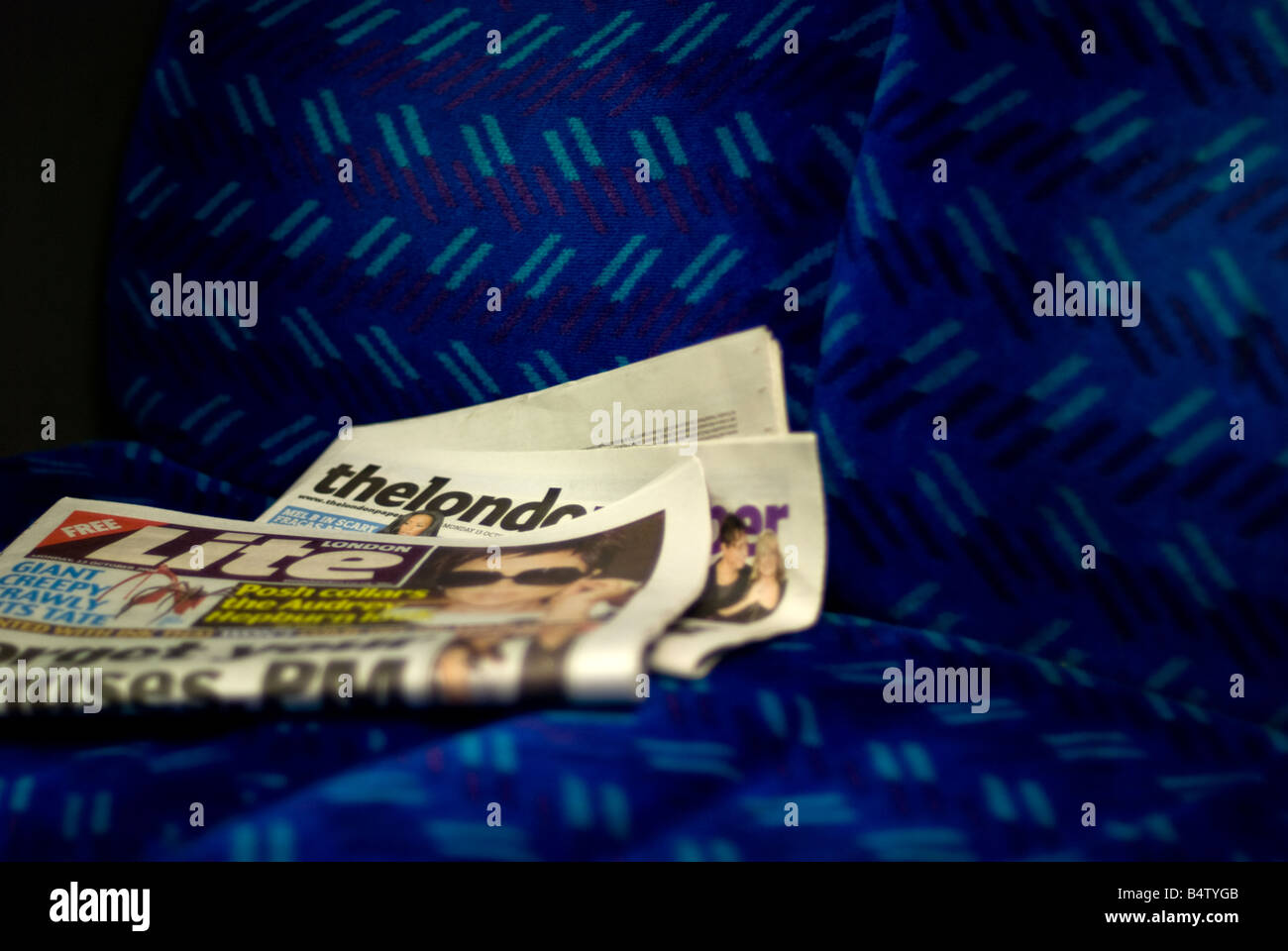 The London Paper and London Lite newspapers disgarded on train seat - Stock Image