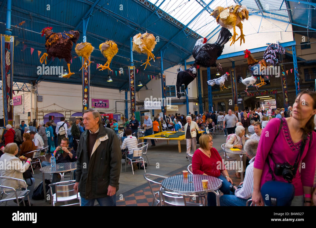 Crowds of people wander sit and browse stalls in Market Hall at Abergavenny Food Festival - Stock Image