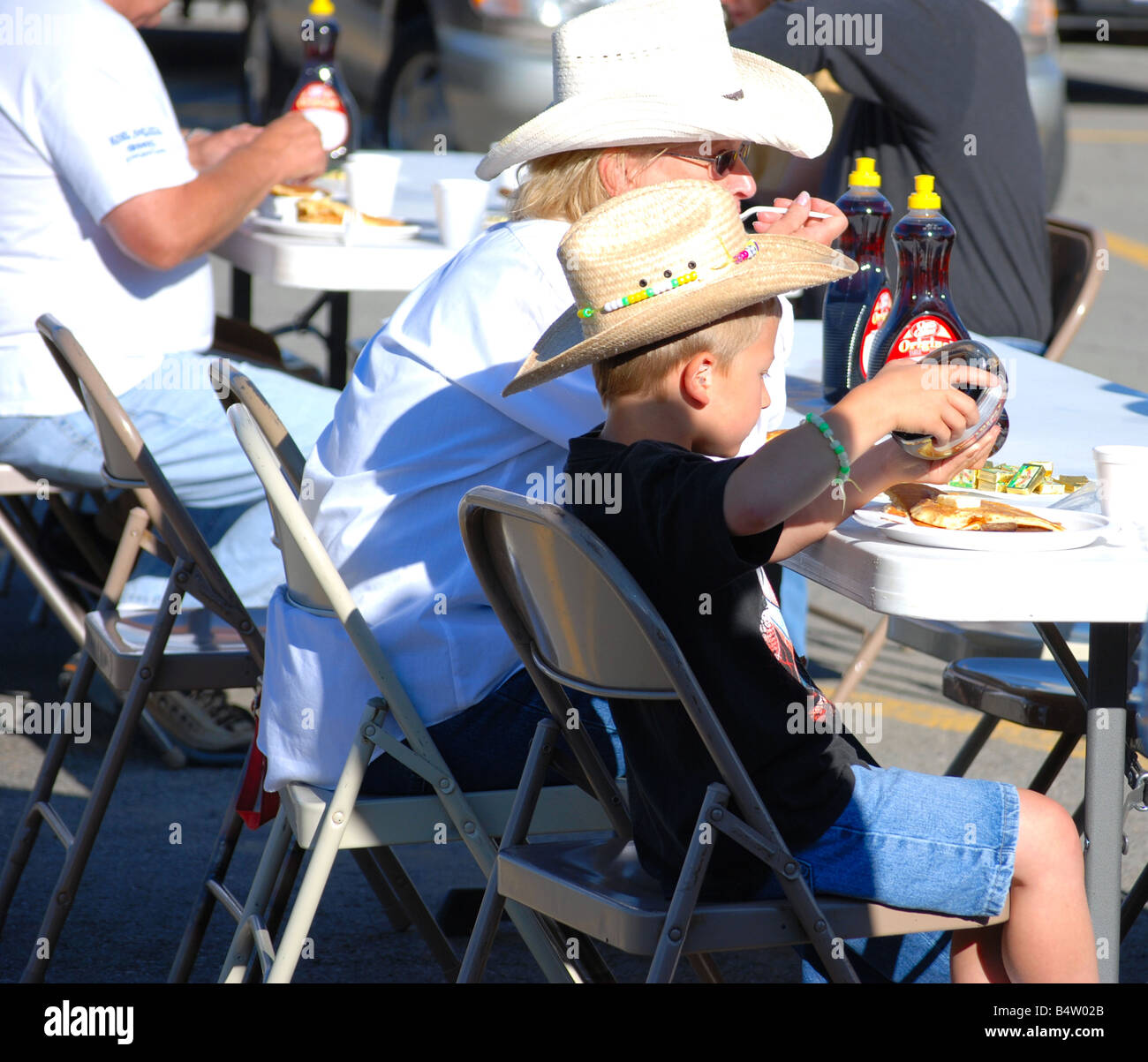 A cowgirl grandma eating pancakes with her grandson at a rotary club pancake breakfast - Stock Image