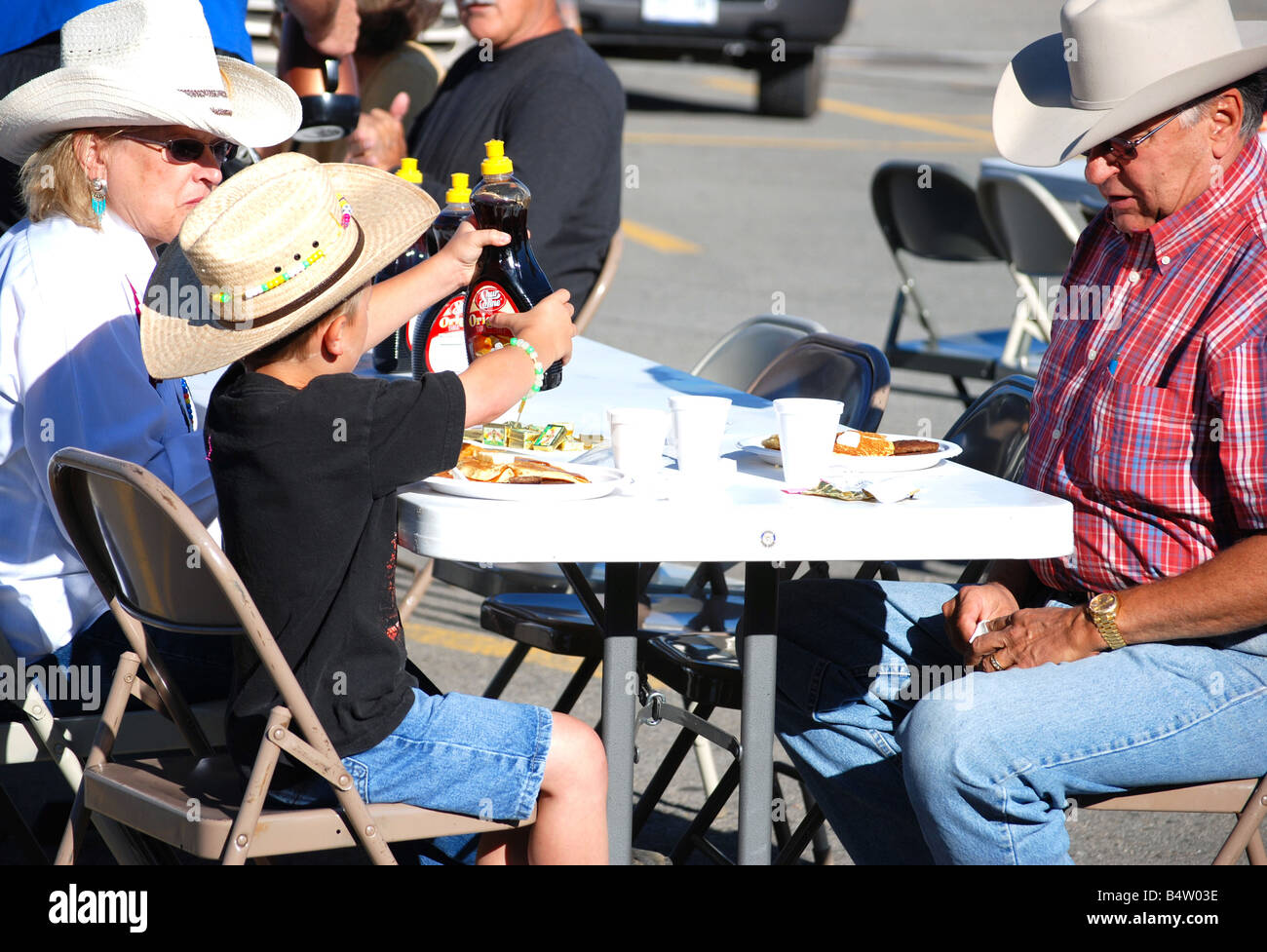 A cowboy and his wife eating pancakes with their grandson at a rotary club pancake breakfast - Stock Image