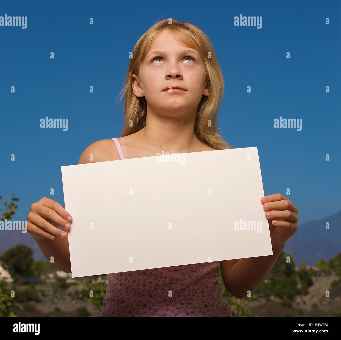 Young girl holding blank sign looking up toward the sky. - Stock Image