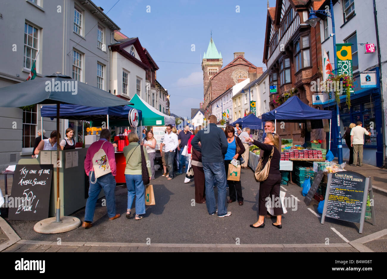 Crowds of people browse street stalls at Abergavenny Food Festival Market Hall in background - Stock Image