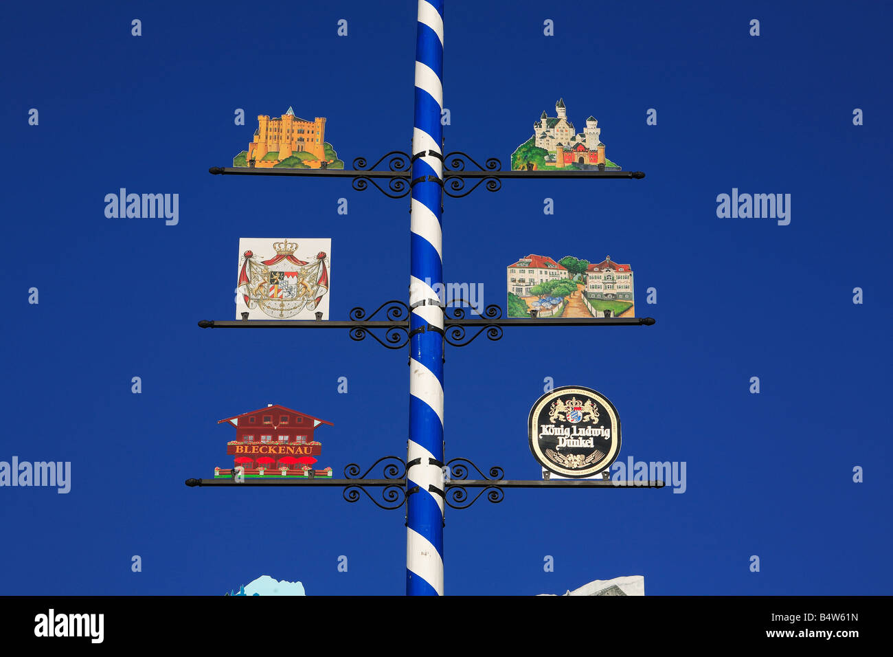 bavarian maypole with signs for the castles of Neuschwanstein and Hohenschwangau - Stock Image