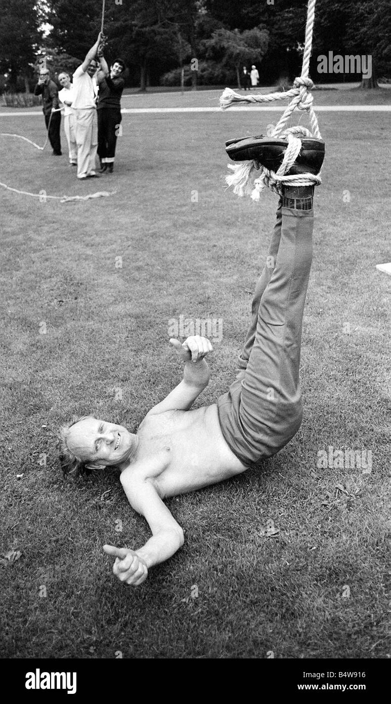 Upside Down Straight Jacket Escape man tied up hanging upside down by a rope August 1968 - Stock Image