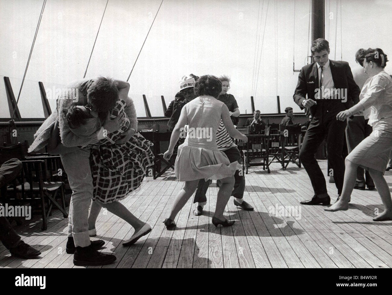 boat party couples dance and jive in true 60 s style Couple kissing doing the twist having fun humour ecard02 - Stock Image