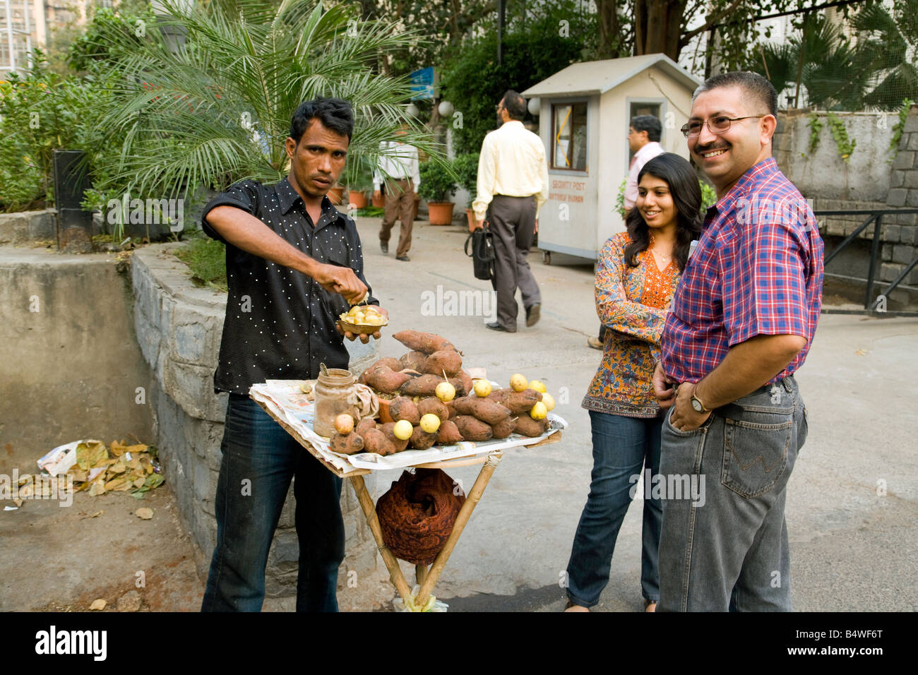 A street trader sells sweet potato to passers by, New Delhi, India - Stock Image