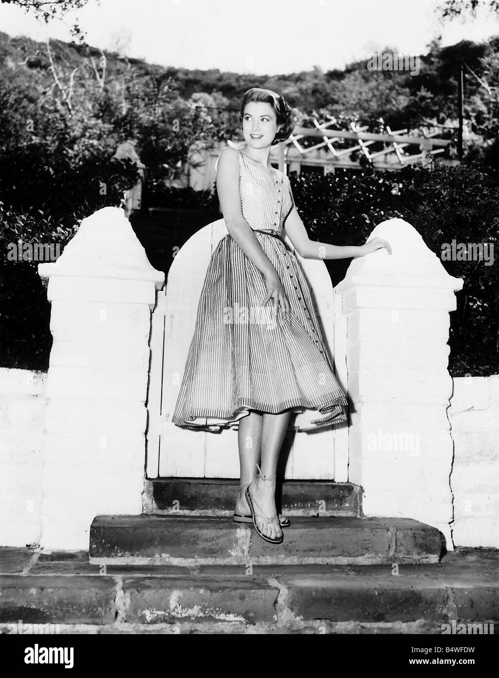 Grace Kelly actress at garden gate in her Hollywood home dress sandals - Stock Image