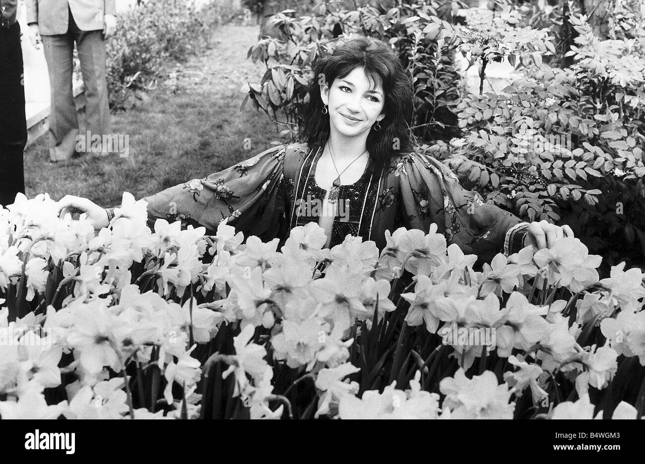 Pop singer Kate Bush poses in a garden full of daffodils and trees December 1979 - Stock Image