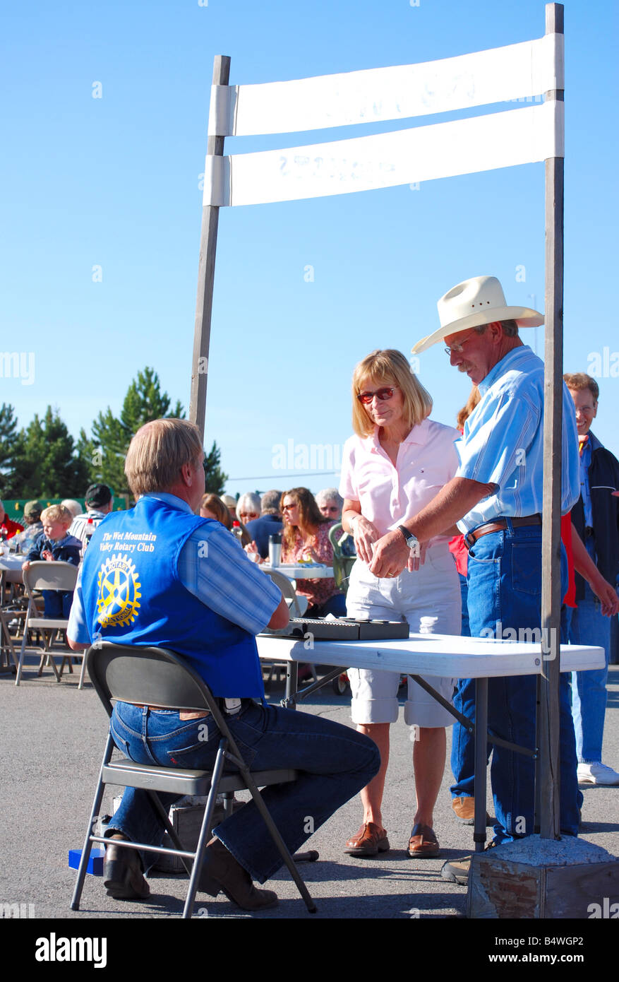 Cowboy and his wife buying tickets for a rotary club pancake breakfast - Stock Image