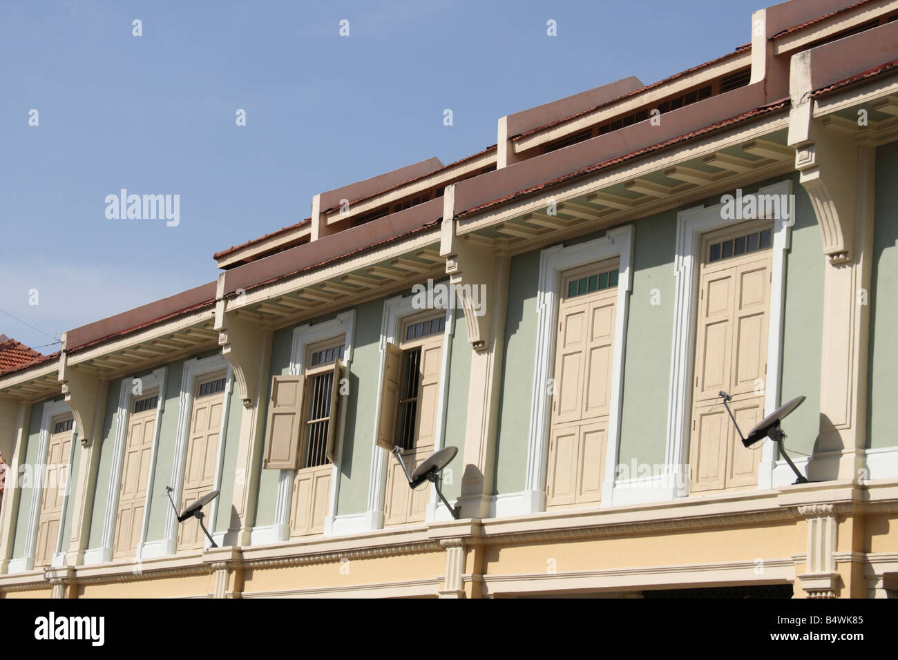 row of window of colonial shophouses in Penang, Malaysia  each having a satellite dish - Stock Image