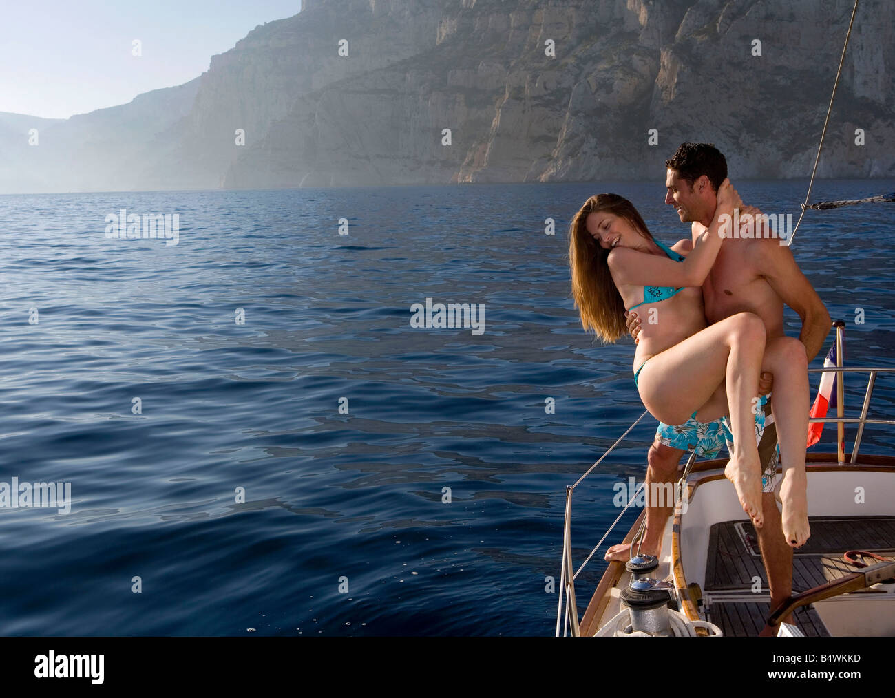 Man lifts girl to sailboats edge - Stock Image