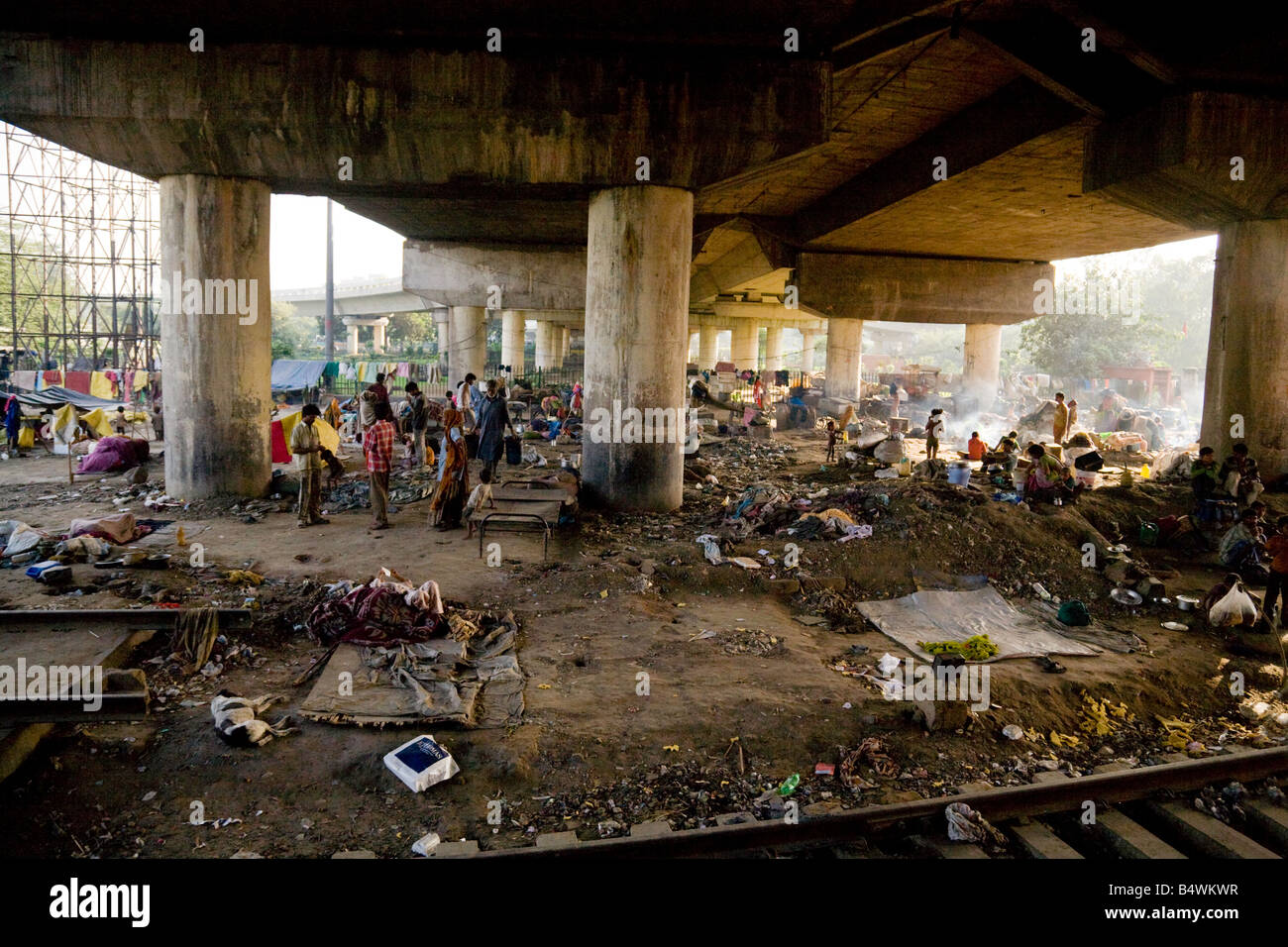 Crowds of people living in slums under the bridge by the Delhi to Bharatpur railway line, New Delhi, India - Stock Image