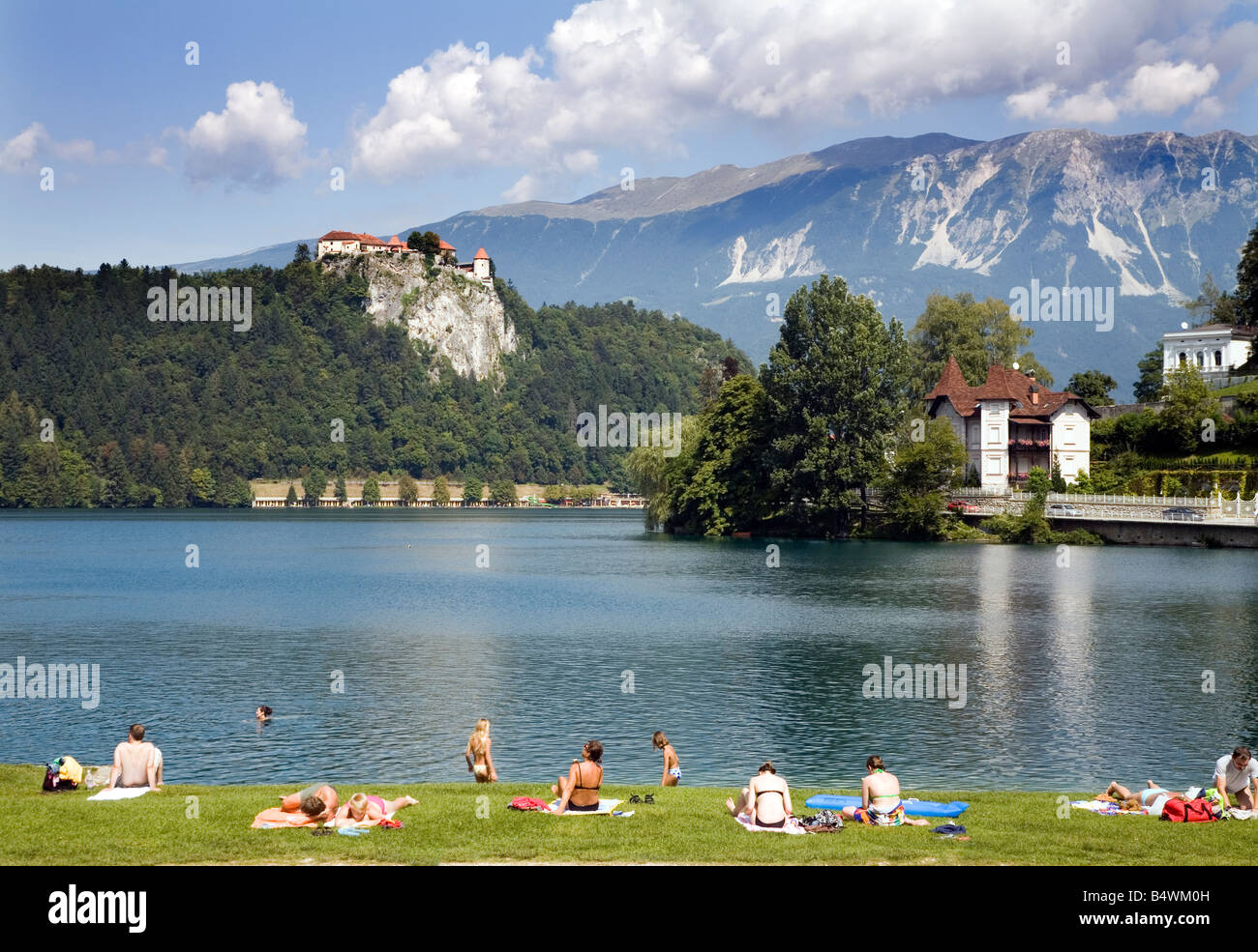 Lake Bled Republic of Slovenia Europe People bathing and sunning on the banks of the lake - Stock Image