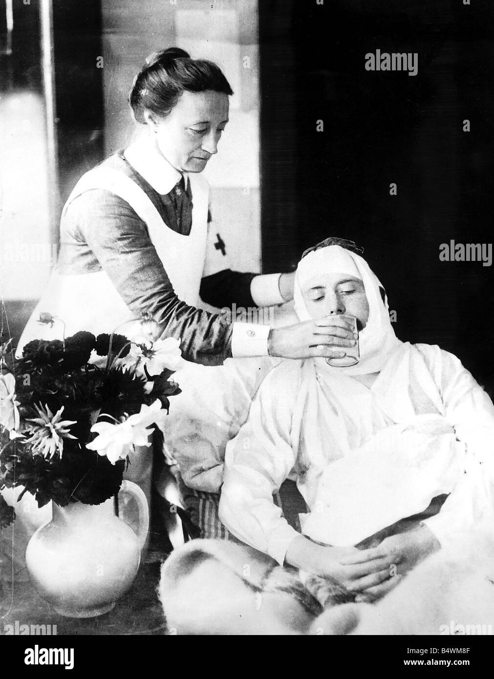 A Red Cross nurse tends to the needs of a soldier wounded in the Somme campaign of 1916 Red Cross nurse gives a - Stock Image