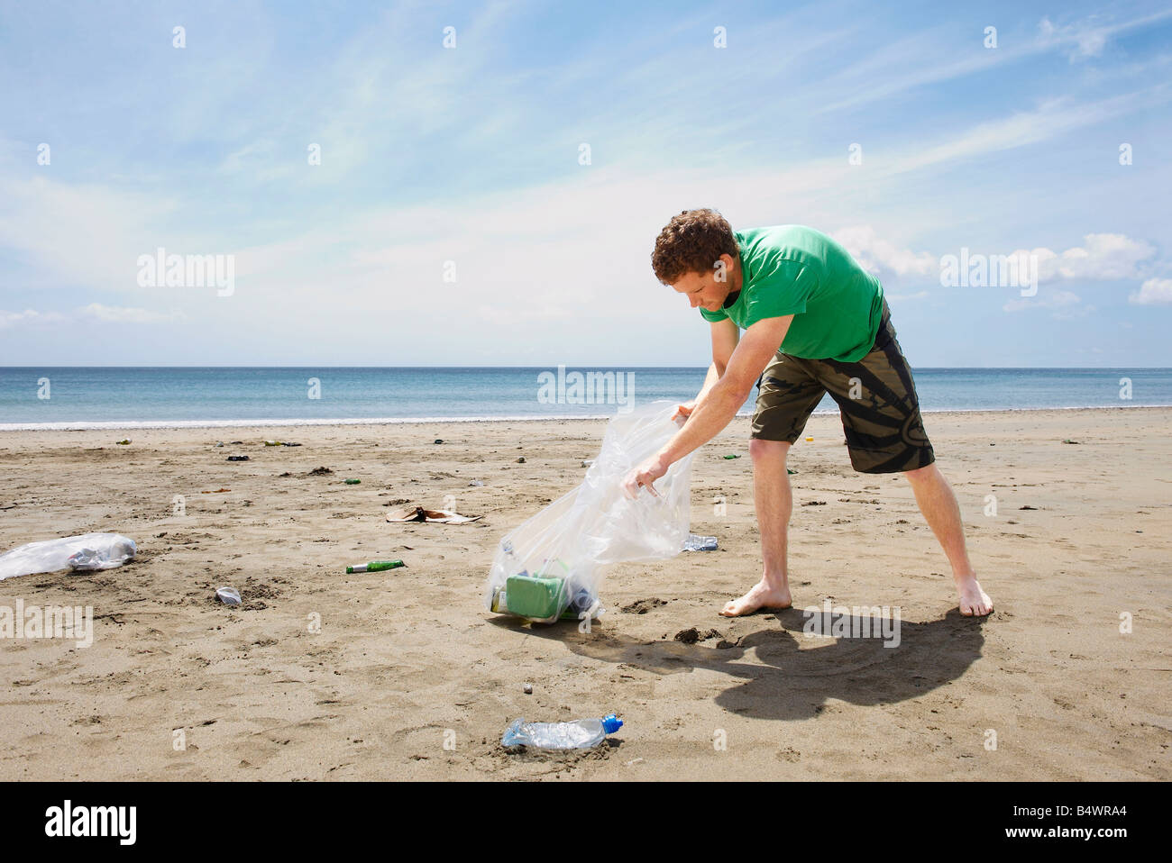 Young man collecting garbage on beach - Stock Image
