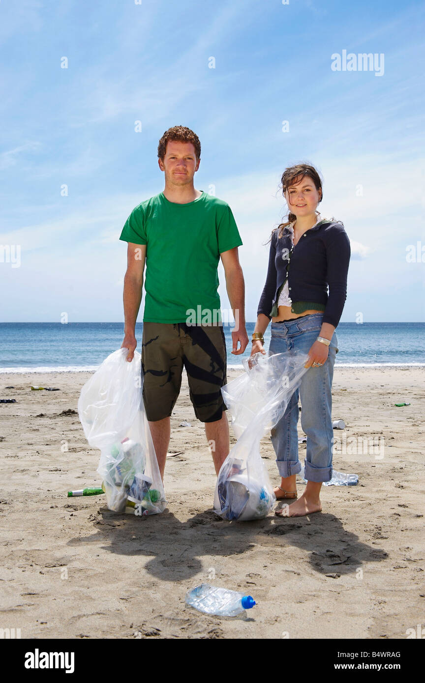 Young couple collecting garbage on beach - Stock Image