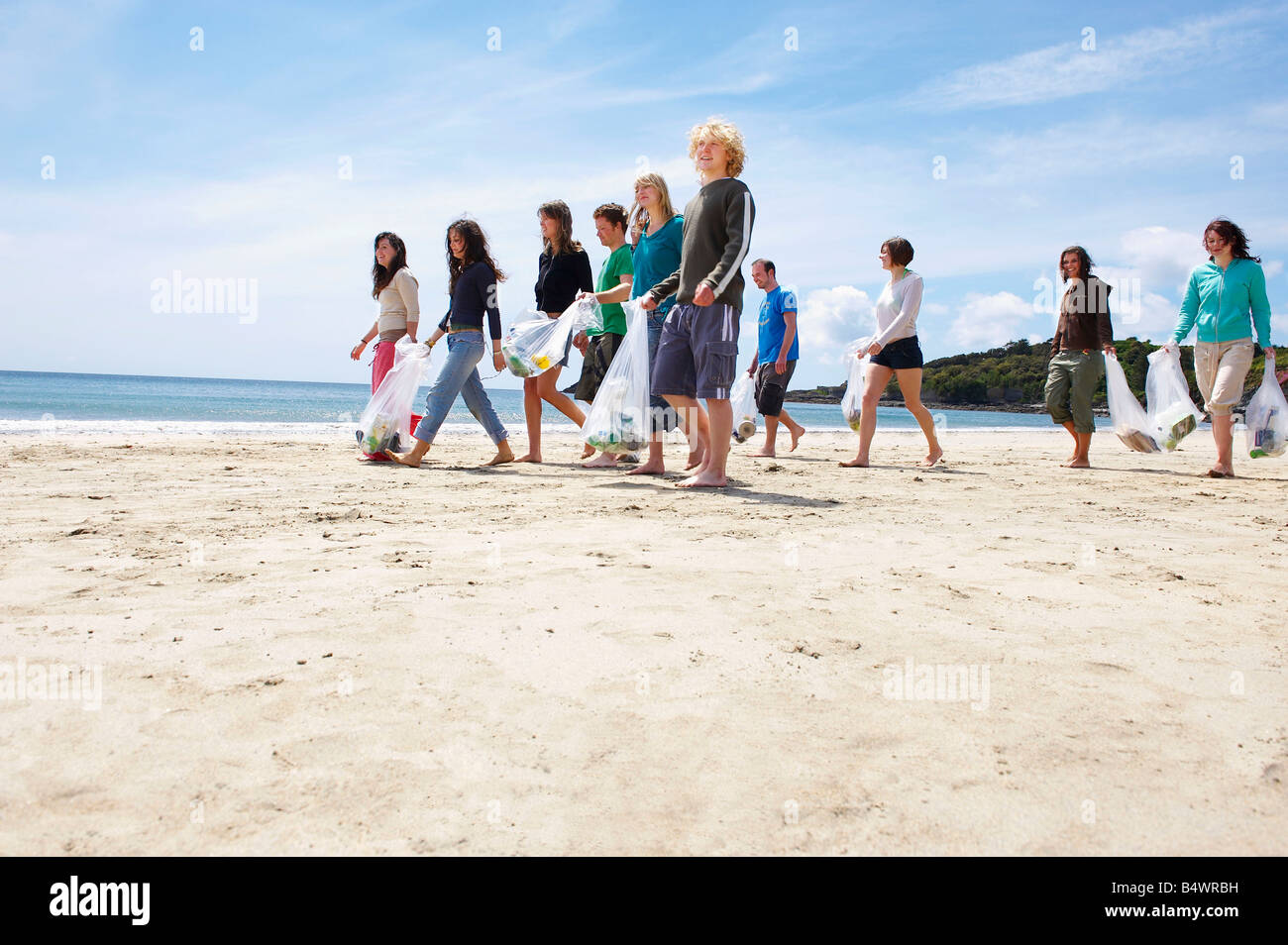 Young people collecting garbage on beach - Stock Image