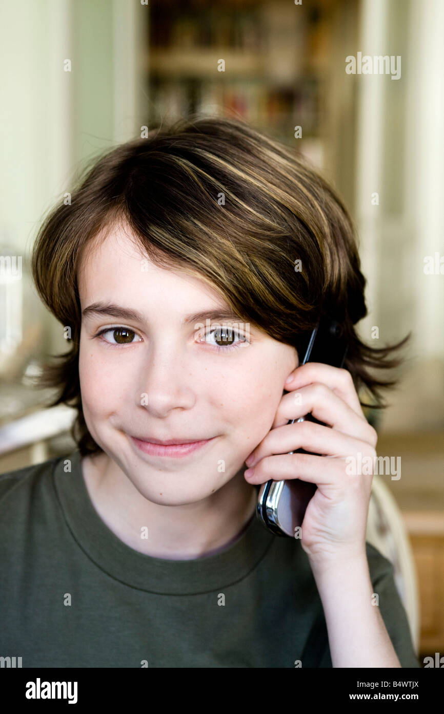 Boy is phoning with his mobile phone - Stock Image