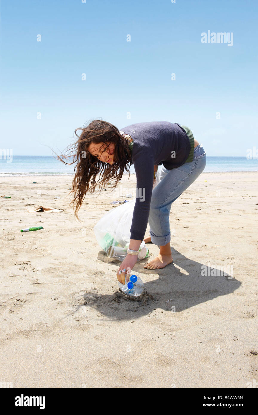 Young girl collecting garbage on beach - Stock Image