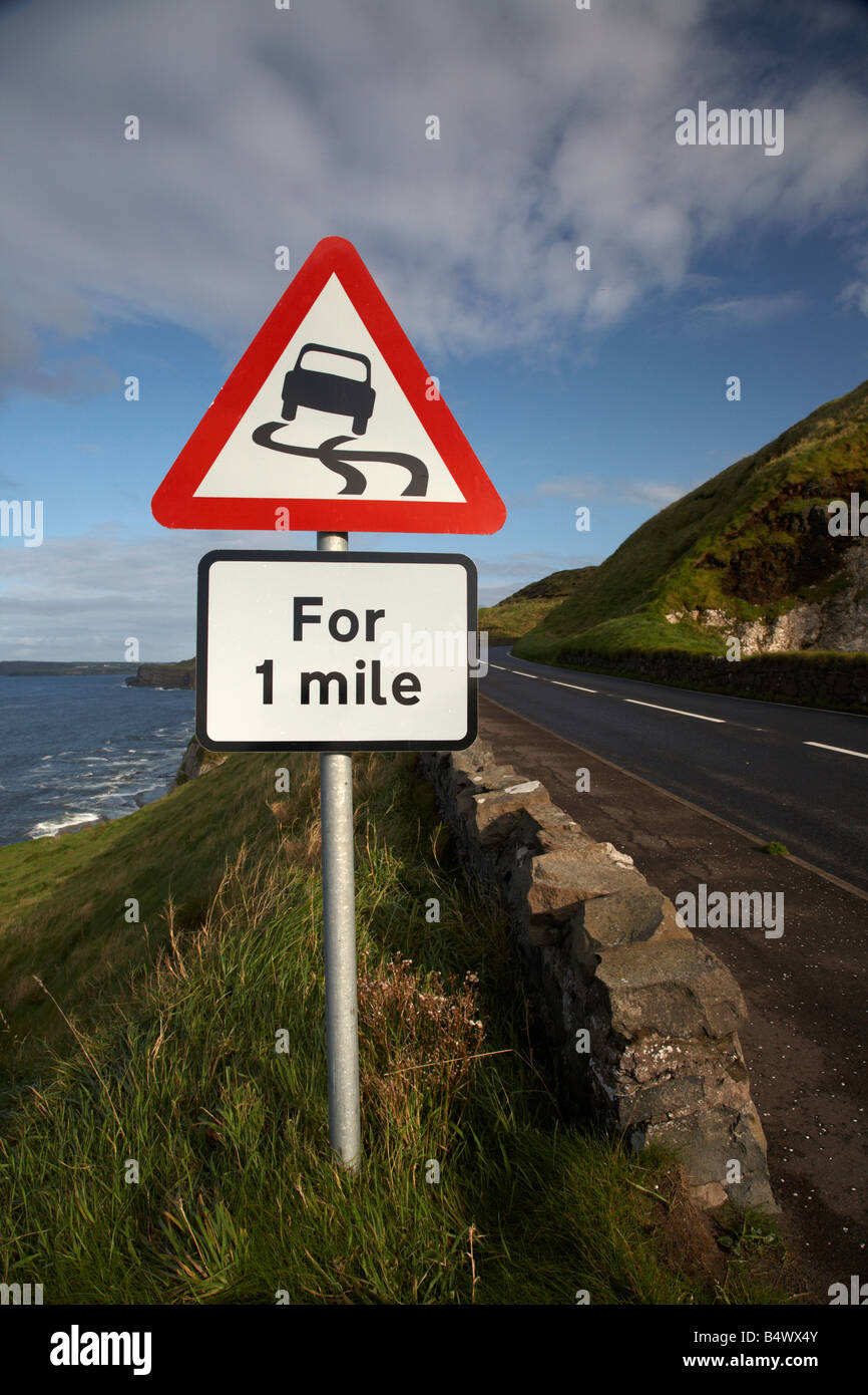slippery road danger red warning triangle for 1 mile sign on the famous A2 north antrim causeway coastal road route Stock Photo