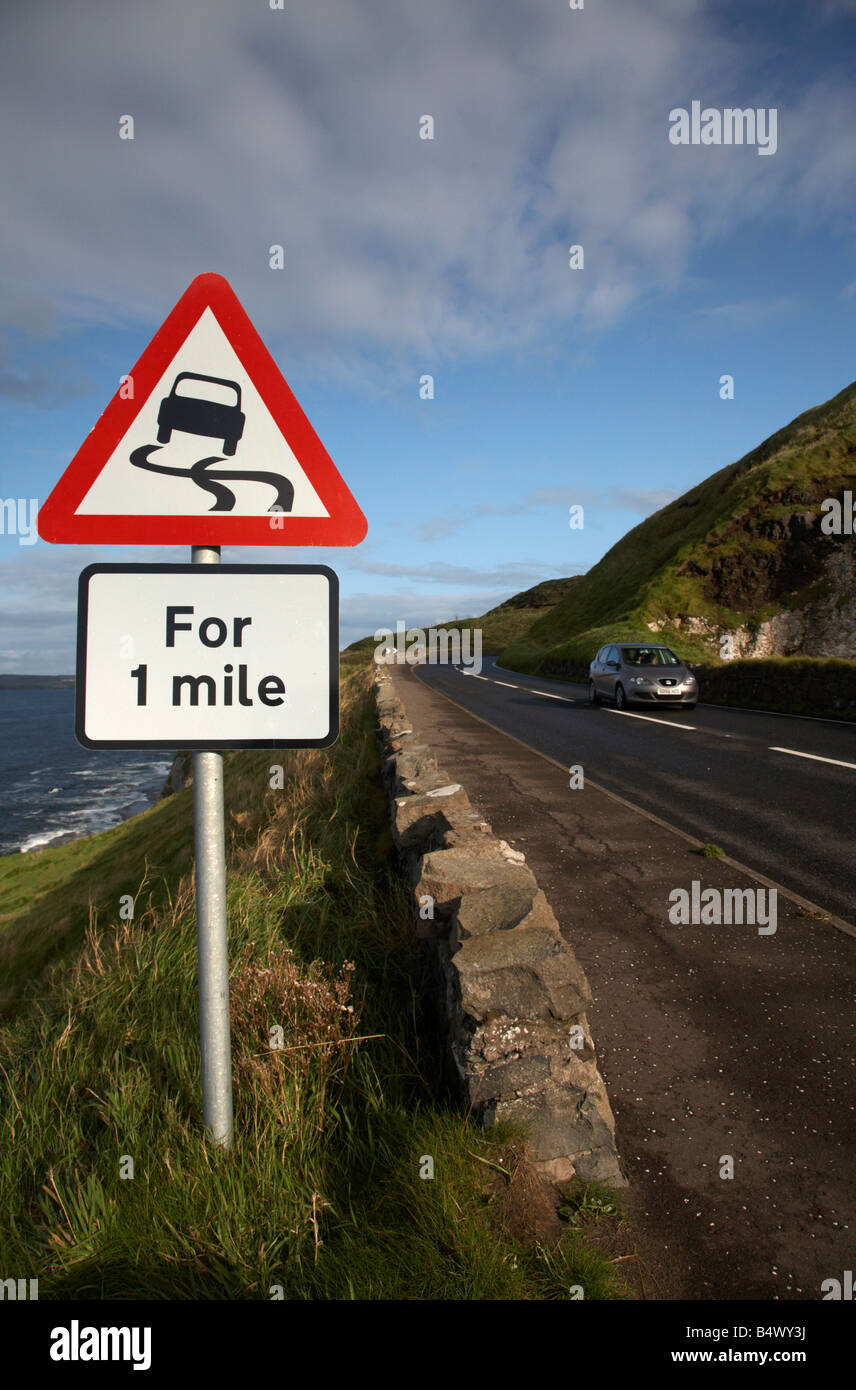 car travelling past the slippery road danger red warning triangle for 1 mile sign on the famous A2 north antrim Stock Photo