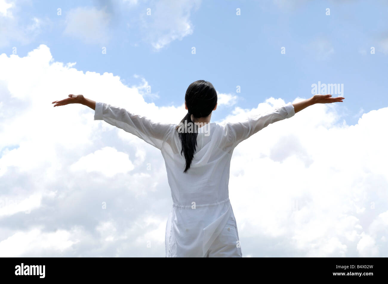 Woman opening her arms against sky - Stock Image