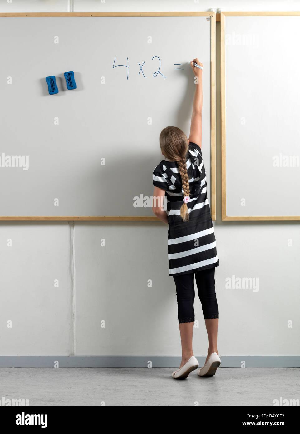 Girl writing on whiteboard - Stock Image