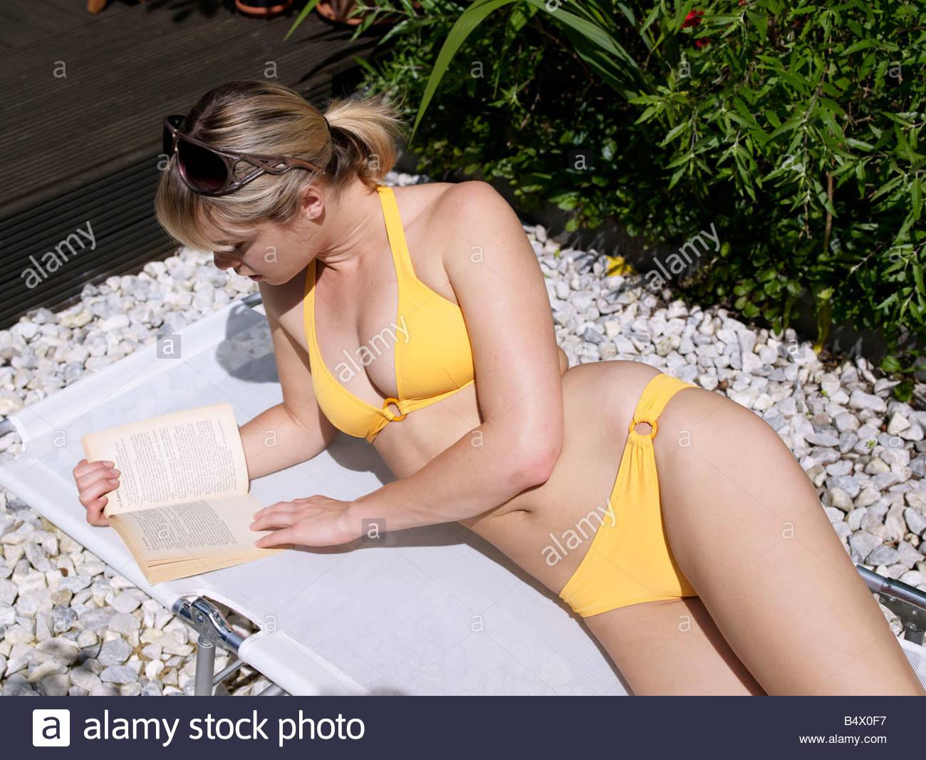 Young woman in bikini in garden reading - Stock Image