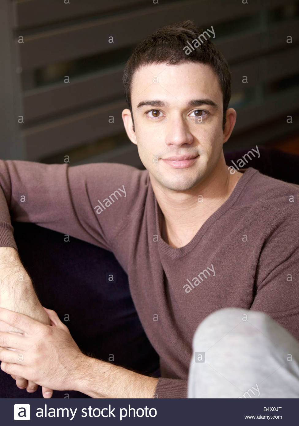Young man sitting relaxed and casual - Stock Image