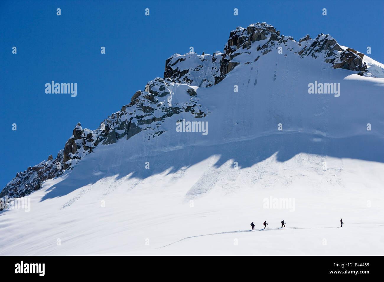 Silhouetted ski tourers on the mountain - Stock Image