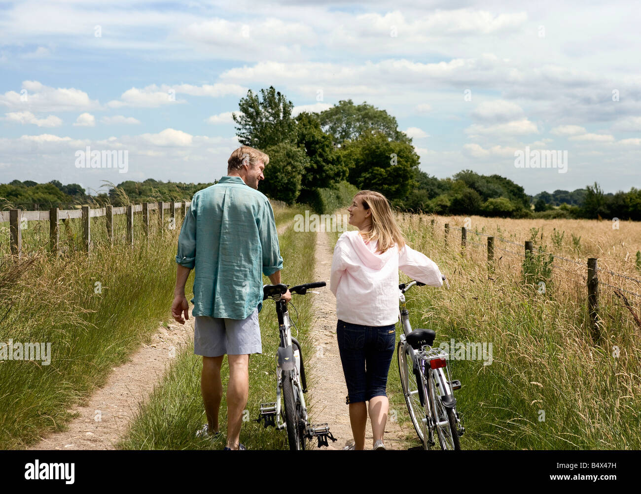 Couple walking with cycles - Stock Image
