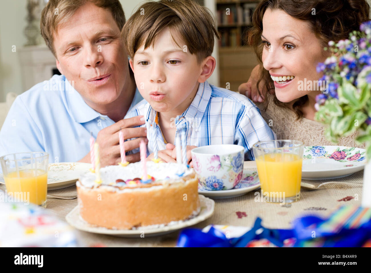 Boy blow out his birthday candles - Stock Image