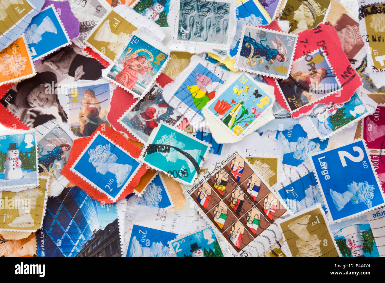 A colourful selection of various used British Royal Mail postage stamps in close-up. England UK Britain - Stock Image