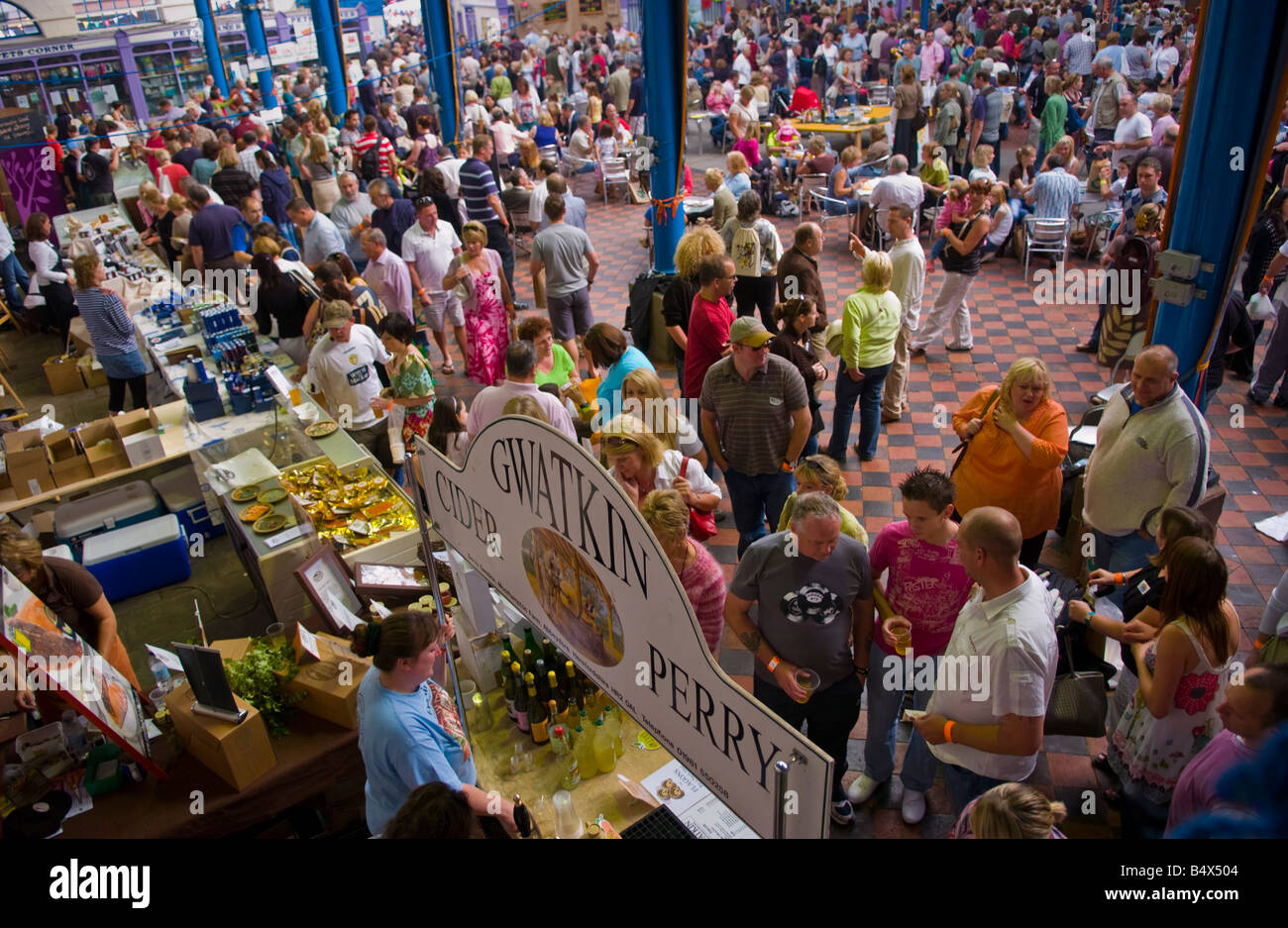 Crowds of people wander sit and browse stalls ain Market Hall at Abergavenny Food Festival - Stock Image