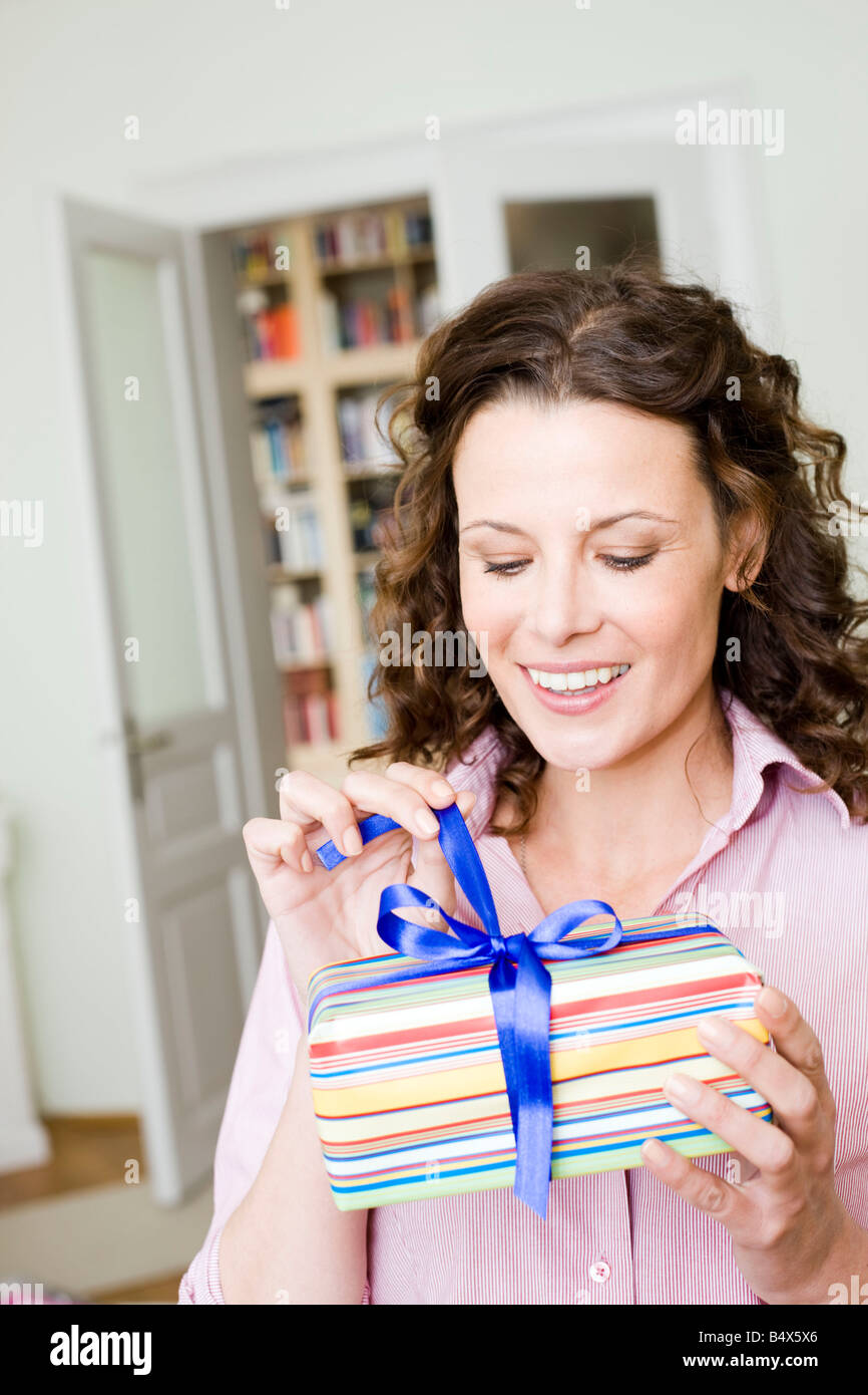 Woman opening a birthday present - Stock Image