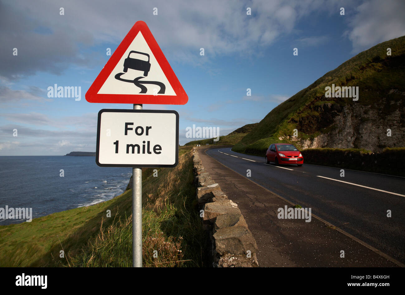car travelling past the slippery road danger red warning triangle for 1 mile sign on the famous A2 north antrim - Stock Image