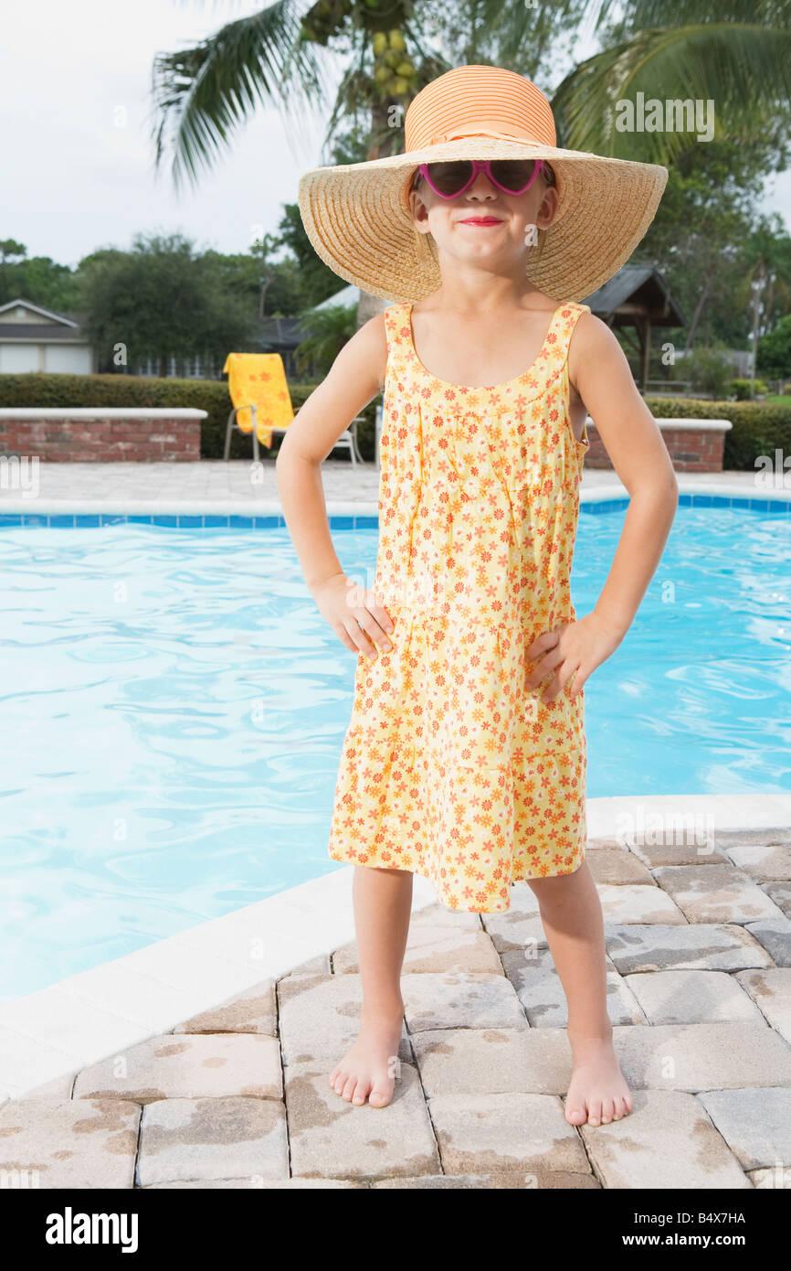 Sassy girl standing at edge of swimming pool - Stock Image