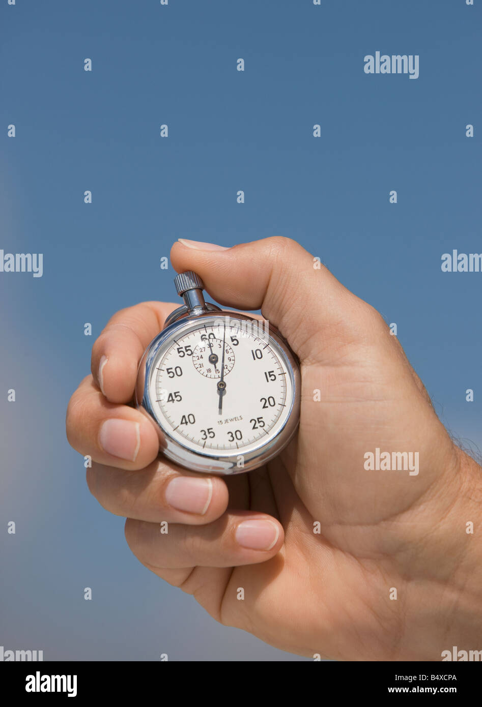 Close up of hand holding stopwatch - Stock Image