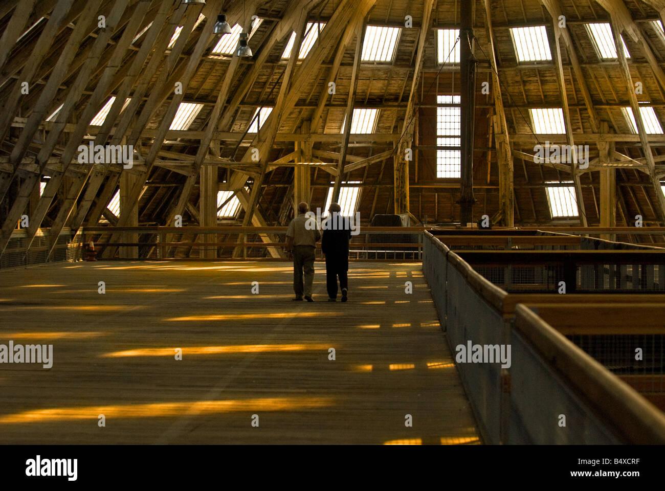 Two men walking along the mezzanine floor of No 3 Slip Cover Chatham Historic Dockyard in Kent. - Stock Image