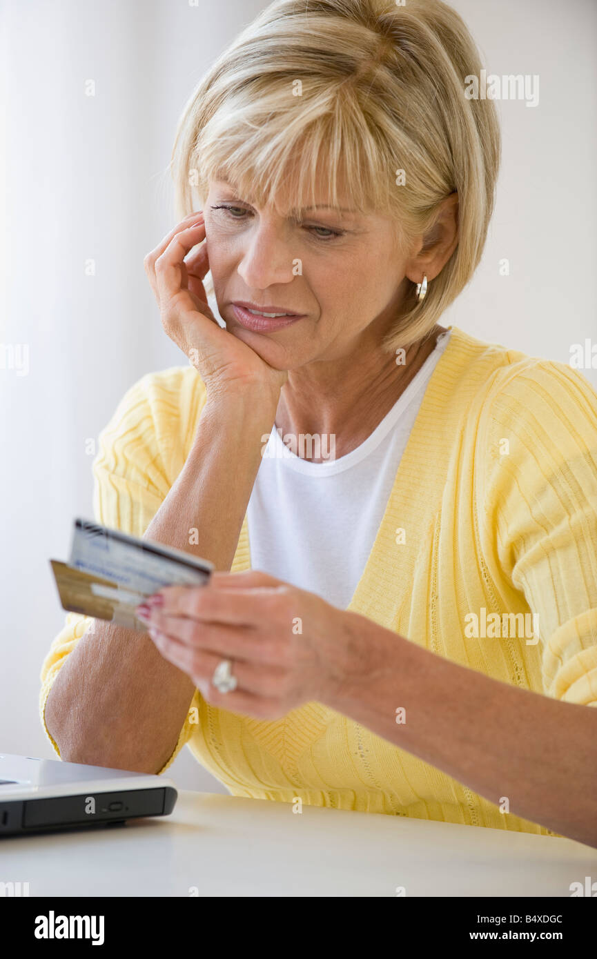 Woman looking at credit cards with concern - Stock Image